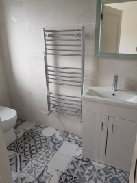 Chrome towel rail and vanity unit in a new bathroom installation in a Carrick-on-Shannon home by North West Tiles & Timber, Ireland