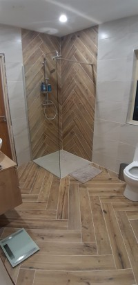 Herring bone timber effect floor and shower tiles,  shower, toilet and vanity unit in a Sligo home installed by North West Tiles & Timber, Ireland