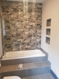 Stone effect wall tiles and inset bath in a new bathroom installation in Leitrim home by North West Tiles & Timber, Ireland